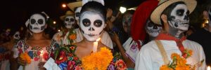 People wearing sugar skull makeup taking part in a Day of the Dead parade