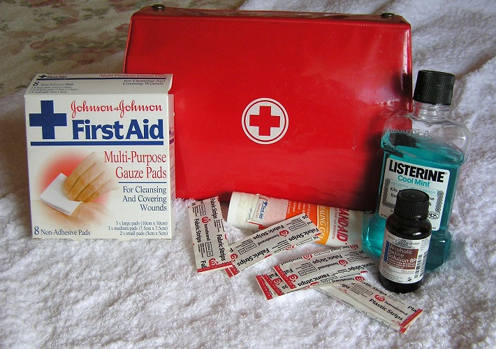 A first aid kit on a bed, with plasters and mouthwash ready to be packed inside
