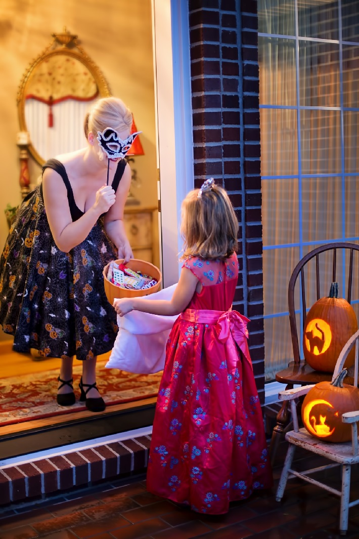 A little girl dressed as a princess being given candy at the house of a woman in Day of the Dead costume