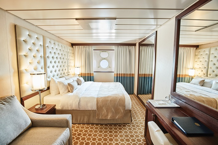 A plush, gold-toned Oceanview stateroom on-board Pacific Princess