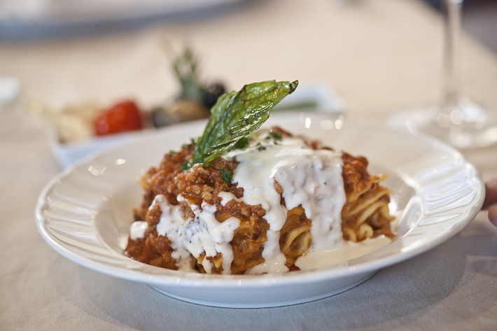 A slice of lasagna with a rich cheese sauce in a bowl in Independence of the Seas' Giovanni's Table restaurant
