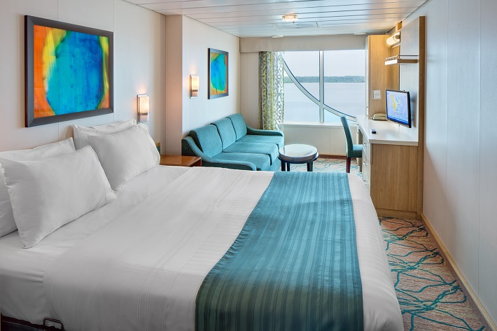 Bedroom and sitting area in an Oceanview stateroom on-board Independence of the Seas