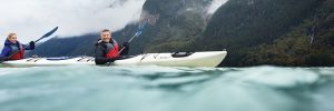 A couple kayaking on choppy water in Alaska