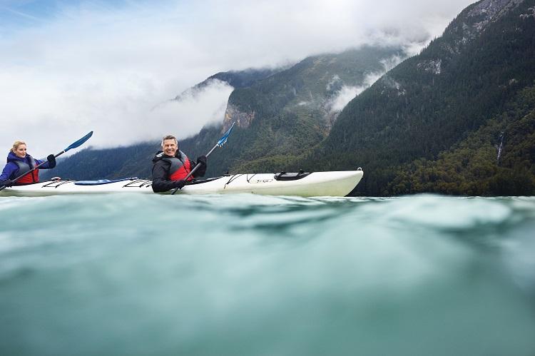 A couple kayaking on choppy water in Alaska