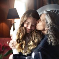 A grandmother affectionately kissing her granddaughter on-board a Princess Cruises ship