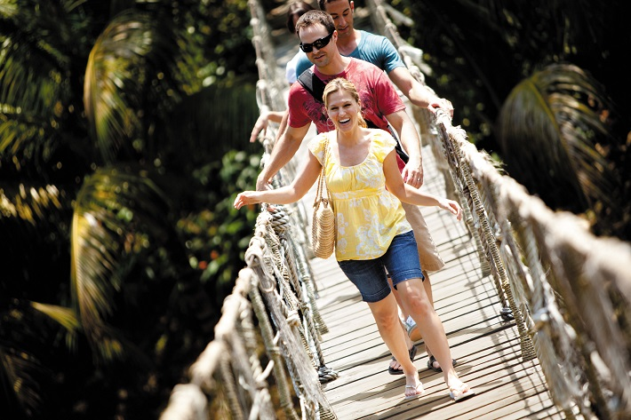 A family walking along a wooden walkway above the trees in South America