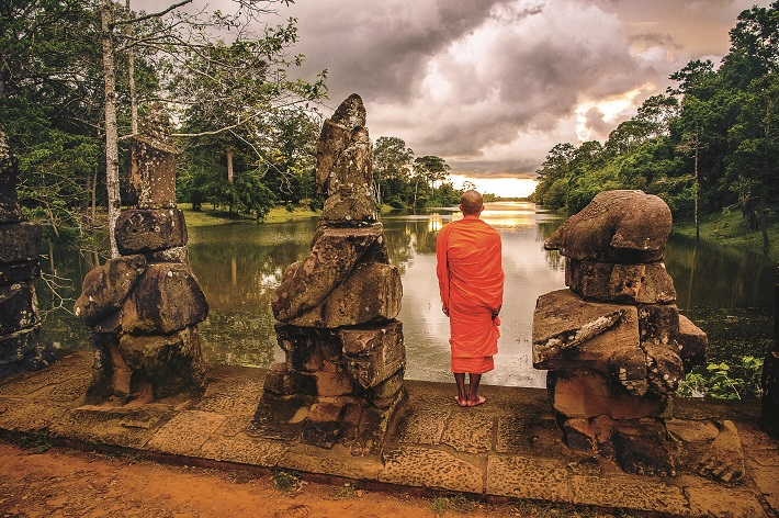 A Buddhist monk standing in front of the Mekong River in Cambodia