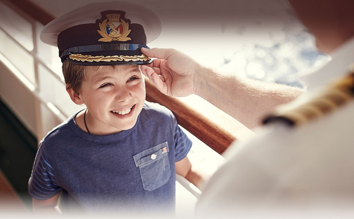 The captain of P&O Ventura putting his hat on the head of a happy child