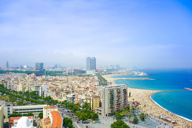 Panorama of Barcelona beach and skyscrapers sitting under a blue sky