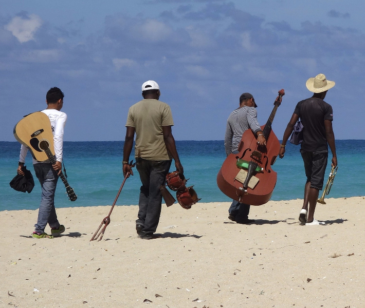 Caribbean locals walking across the beach with musical instruments