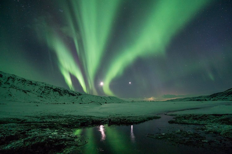 Pale green Northern Lights shining over snow and rivers in Thorsmork in Iceland