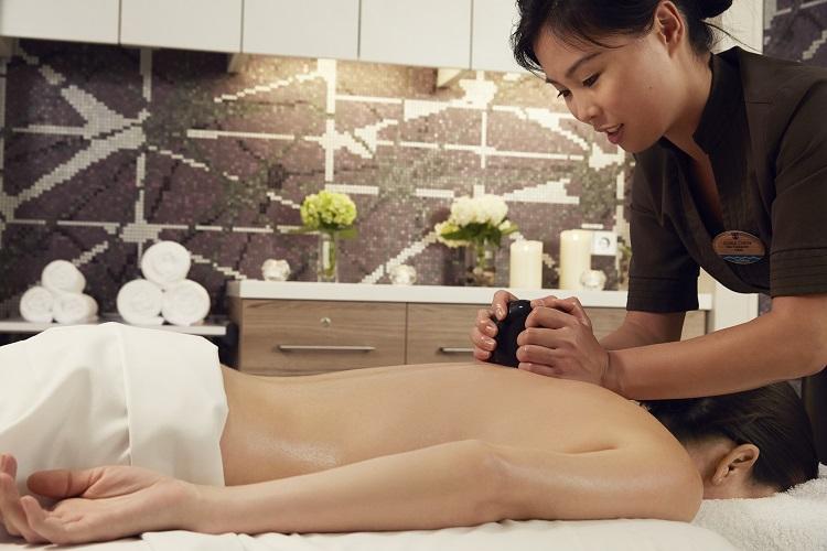 A massage therapist giving a Royal Caribbean cruise passenger a massage