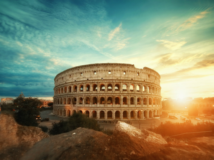 The sun setting behind the Colosseum in Rome during winter