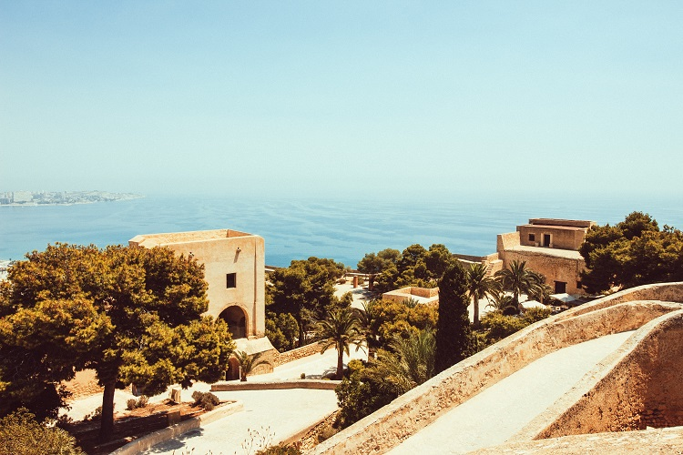 Ancient architecture and lush trees on the coast of Malaga cruise port