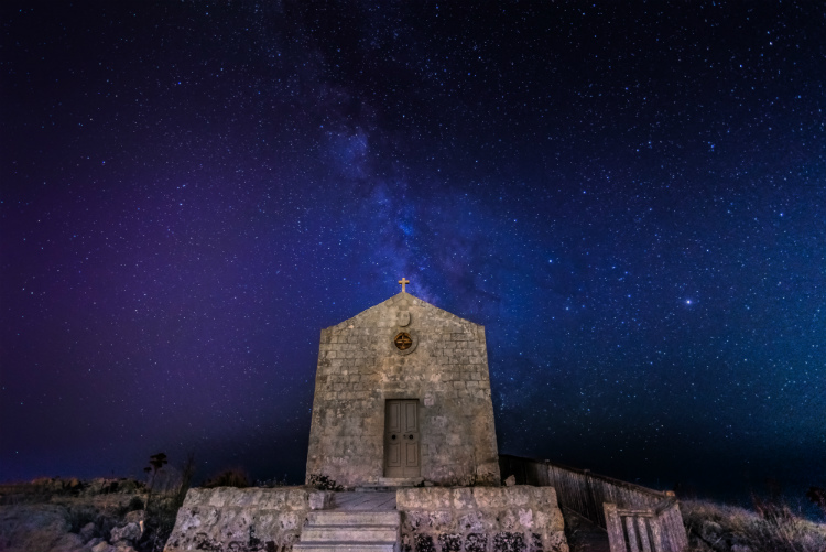 A remote church under a night sky filled with stars and galaxies in Malta