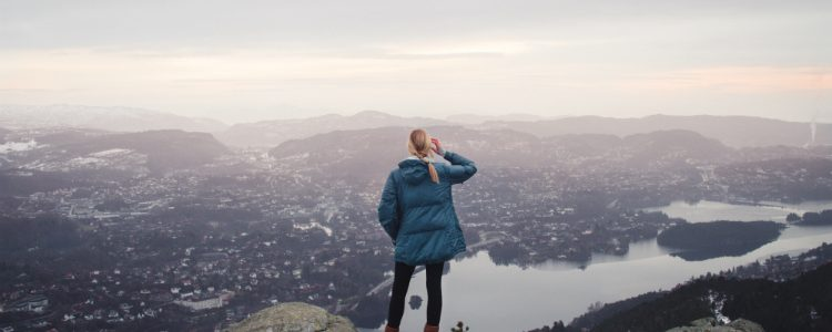 A solo cruise passenger admiring the view from a mountain in Bergen
