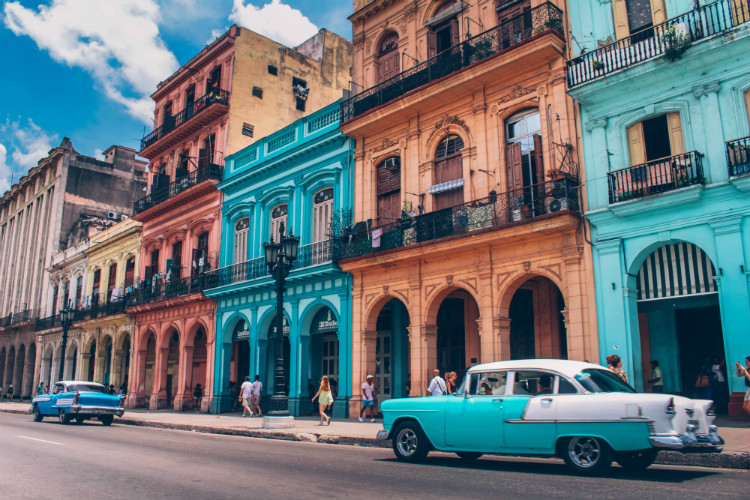 Classic cars parked alongside colourful buildings in Havana in Cuba