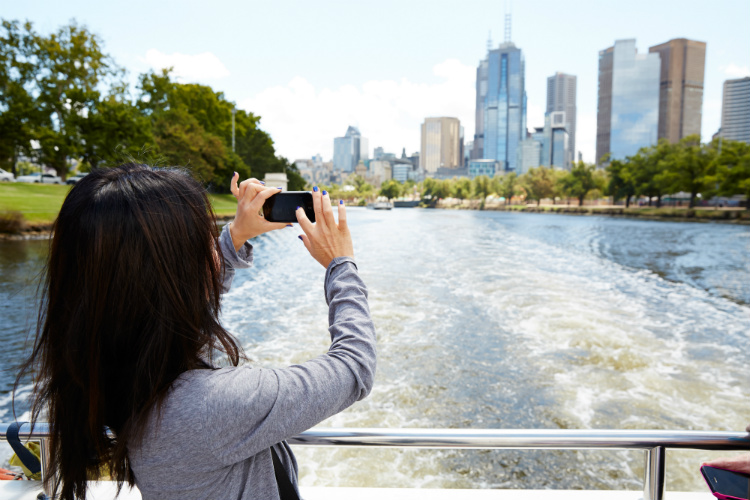 A Princess Cruises passenger taking pictures of Melbourne from a river boat