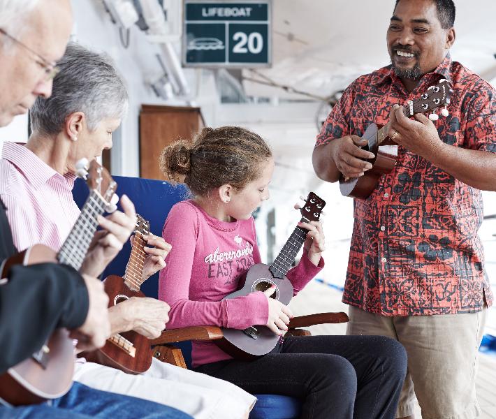 Man teaching guests ukulele on-board Princess