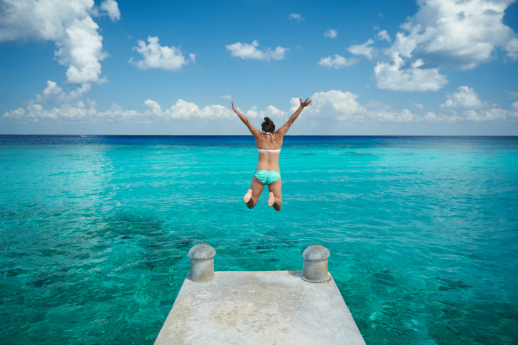 A woman jumping into the bright blue Caribbean sea during a solo cruise