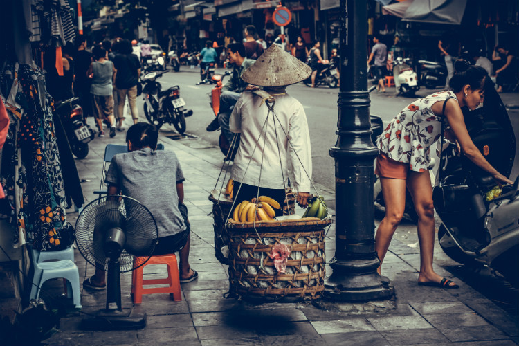 Hanoi locals carrying shopping and selling goods at market