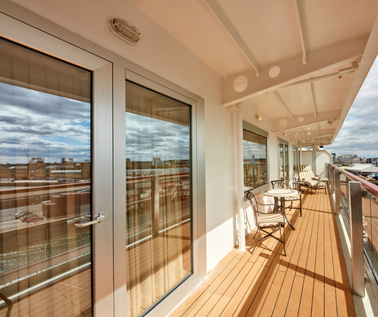 The balcony of a Britannia Club Balcony stateroom bathed in sunshine