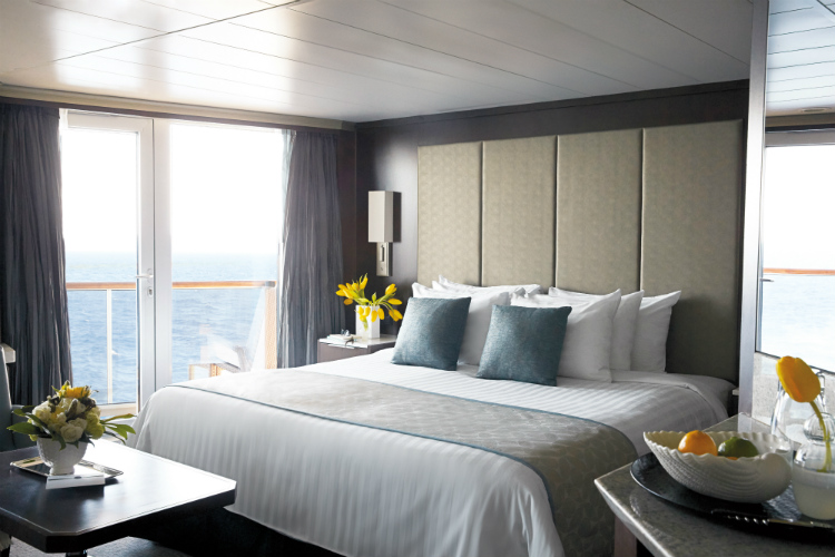 The bedroom of an elegant suite on-board Holland America Line's ms Oosterdam