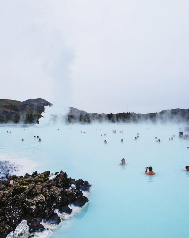 People bathing in the milky blue water of the geothermal Blue Lagoon in Iceland