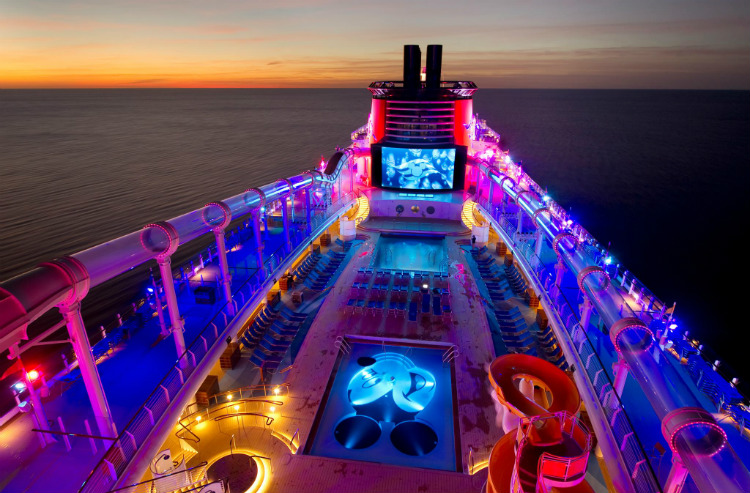 The deck of a Disney Cruise Line ship illuminated by multi-coloured lights at night