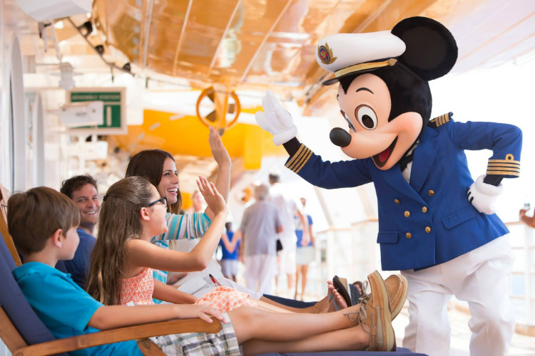 Captain Mickey Mouse high-fiving a family on a Disney Cruise Line ship