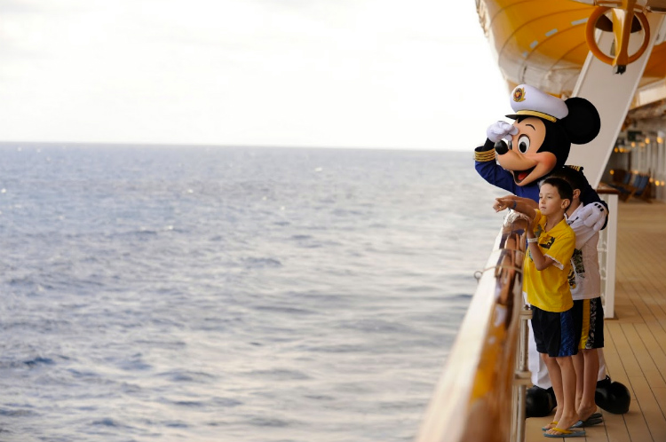 Captain Mickey hanging out with a young guest on the Disney Dream cruise ship