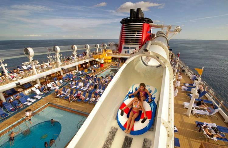 Guests flying down a waterslide in rubber rings on-board Disney Dream
