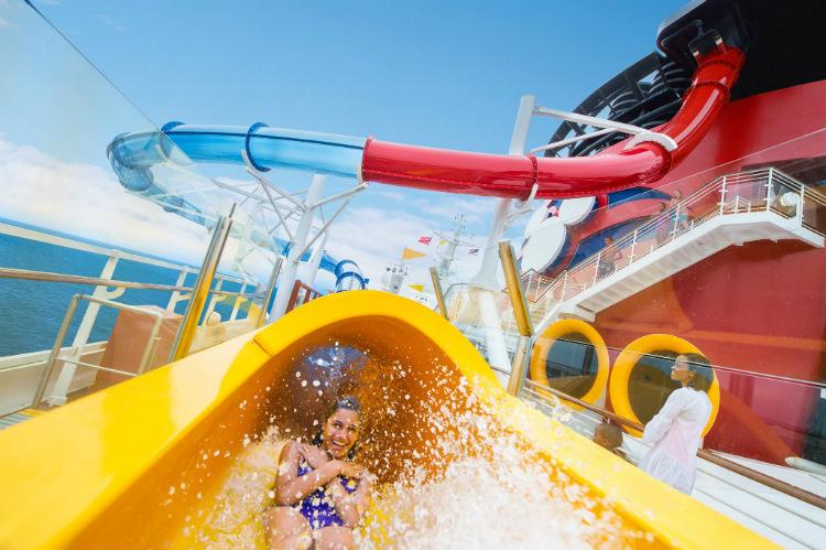 A passenger on a yellow waterslide on-board Disney Dream