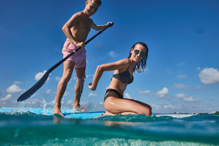 A couple on a paddleboard in the sea in the Caribbean