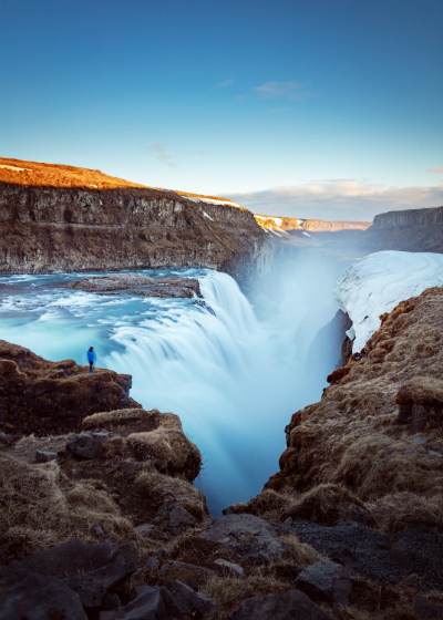 A figure standing next to the thundering Gulfoss waterfall in Iceland