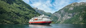Hurtigruten's MS Finnmarken cruise ship sailing through Geirangerfjord
