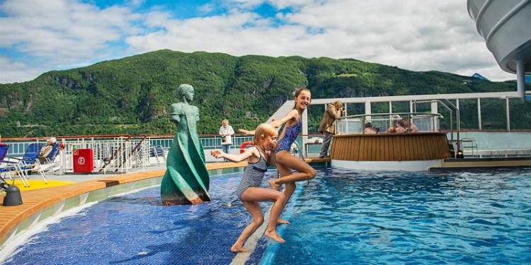 Kids jumping into the swimming pool on-board Hurtigruten's MS Finnmarken