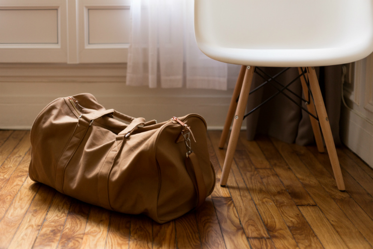A leather duffle bag next to an Eames chair in a hotel room