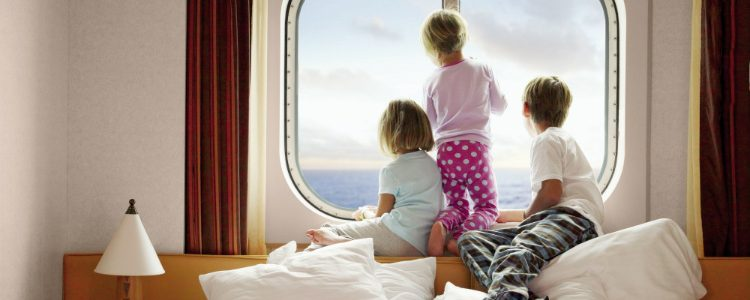 Children gazing out of the window of an outside family stateroom on a Carnival cruise ship