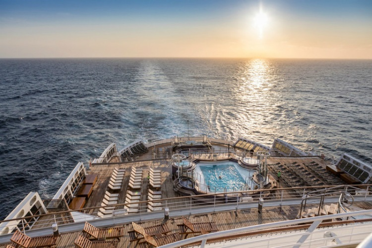 The pool deck of Cunard's Queen Mary 2 at sunset