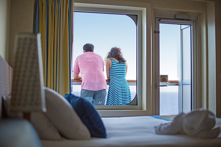 Couple gazing out balcony window on-board Carnival Cruises