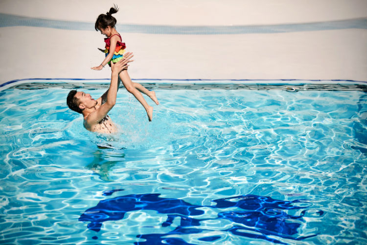Father and daughter swimming in a pool on-board Princess Cruises