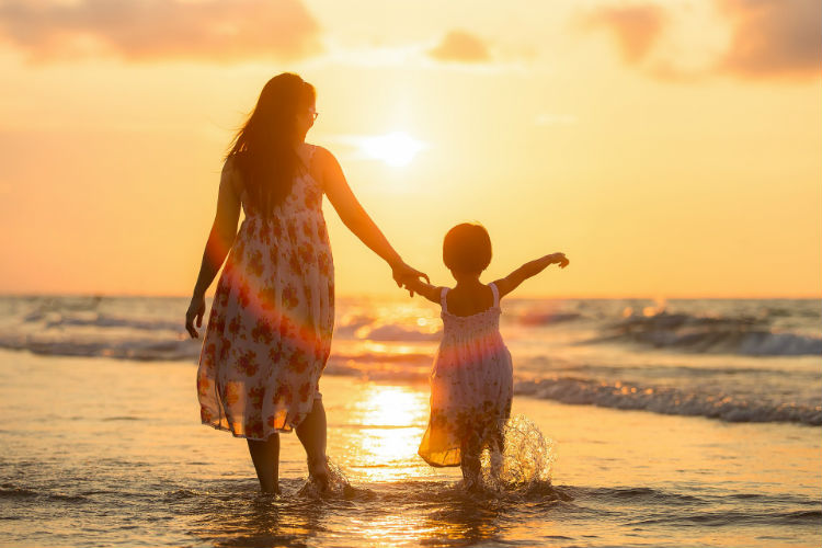 Woman and child walking along the beach in the sunset