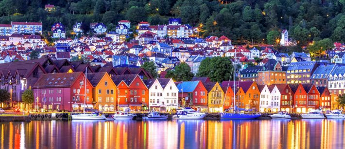 Colourful houses lining a fjord in Bergen at nighttime