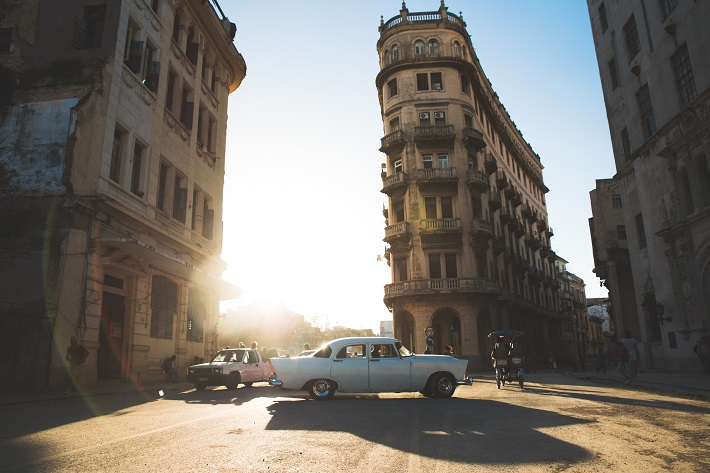 Classic cars driving past beautiful, historic architecture in Cuba
