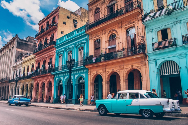 Brightly-coloured buildings and classic cars lining the streets in Cuba