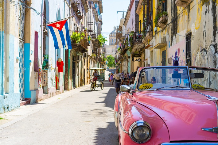 A pink classic car parked on a street in Cuba