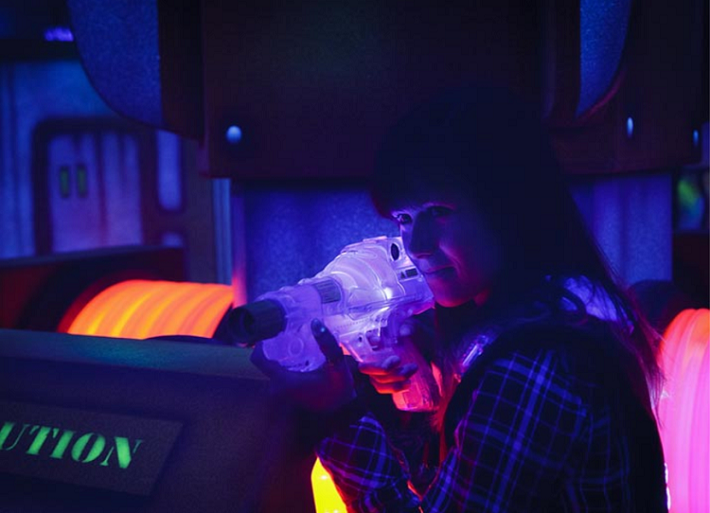 A teenage girl playing laser tag in the neon laser tag game on-board Independence of the Seas