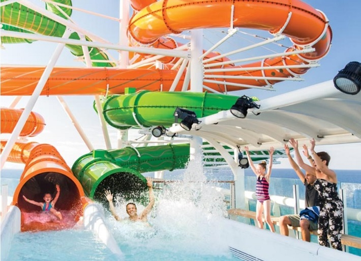 Parents cheering as their kids fly out of water slides on-board Independence of the Seas