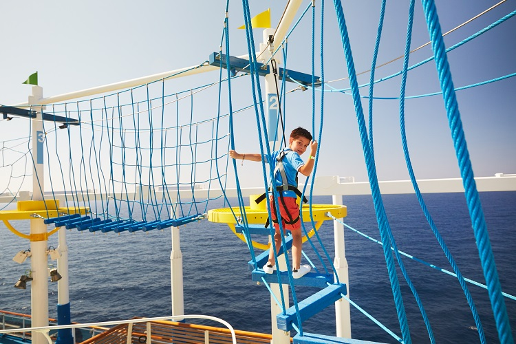 A child using the top-deck ropes course on-board Carnival Panorama